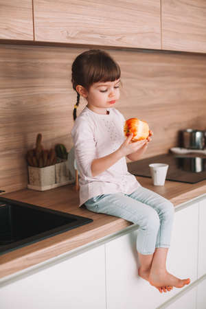 Cute little girl eating red apple sitting on a kitchen surface. Healthy eating concept. Stockfoto