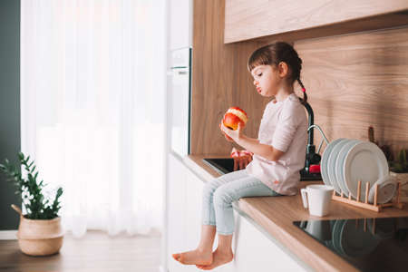 Cute little girl eating red juicy apple sitting on a kitchen. Healthy eating concept. Stockfoto