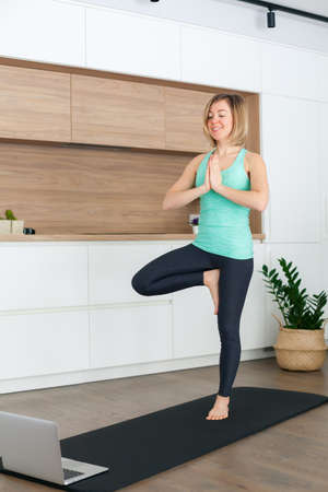 Woman standing in a Tree pose while doing yoga online at home