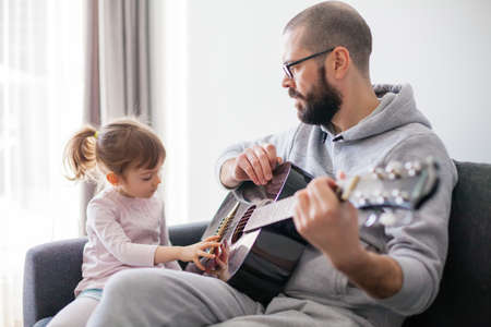 Little girl touching strings of the guitar. Her father is teaching her to play guitar.
