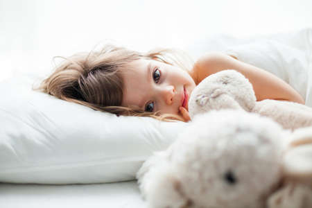 Beautiful little girl with big eyes lying in white bed with rabbit toys near her