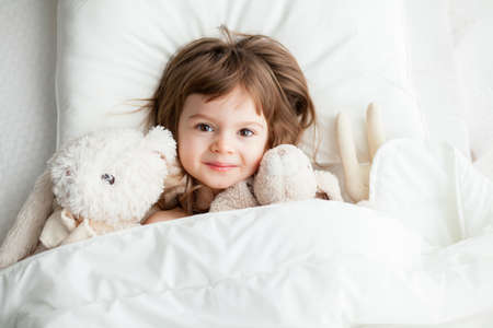 Adorable smiling little girl lying in white bed with rabbit toys