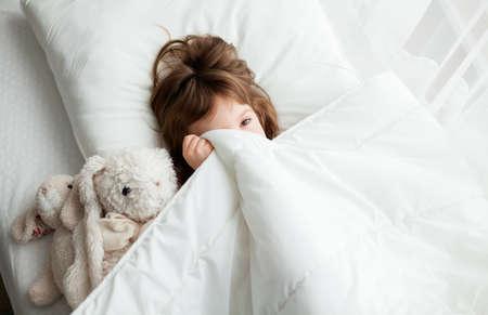 Little girl hiding under white blanket, she's just woke up Stockfoto