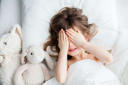Adorable little girl hiding her face behind her hands as she awakened. She's lying in white bed with rabbit toys.