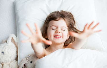 Adorable little girl stretching her hands as she awakened. She's lying in white bed with rabbit toys.