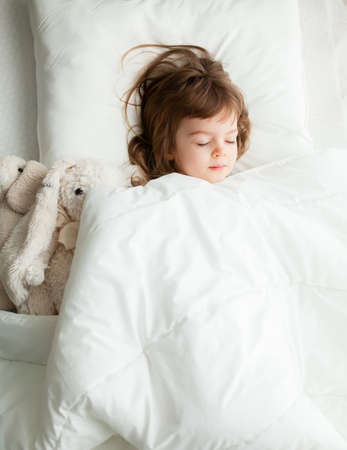 Beautiful little girl sleeping in white bed with rabbit toys near her