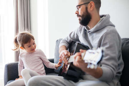 Little girl touching guitar strings while her father playing guitar for her