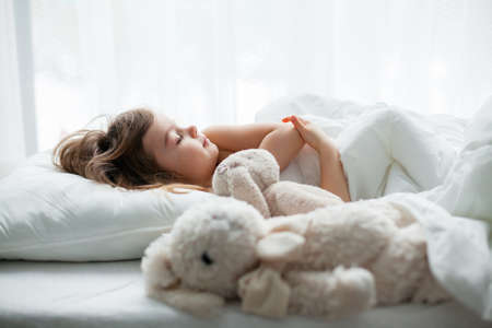 Beautiful little girl sleeping sweetly in a white bed with rabbit toys lying near