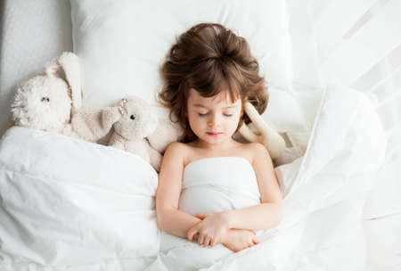 Adorable calm little girl sleeping in white bed with rabbit toys near her Stockfoto