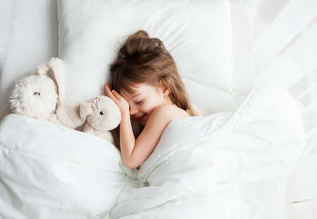 Adorable smiling little girl sleeping in white bed with rabbit toys near her Stockfoto