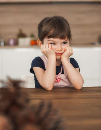 Cute bored little girl sitting at the kitchen table