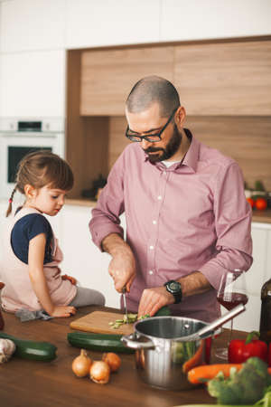 Handsome man and his cute little daughter are cooking vegetable stew together in the kitchen. Healthy and vegetarian food concept.