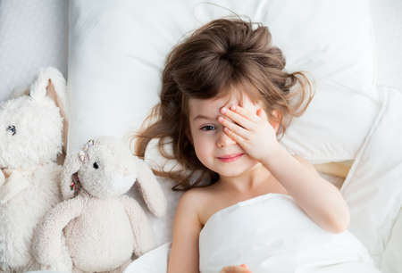 Adorable little girl hiding her eyes behind her hands as she awakened. She's lying in white bed with rabbit toys.
