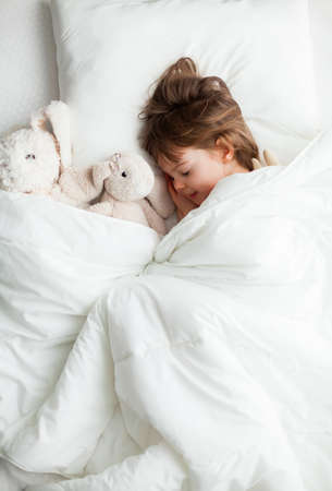 Sweet little girl sleeping in white bed with rabbit toys near her