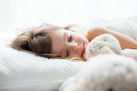 Portrait of a beautiful little girl sleeping sweetly in a white bed