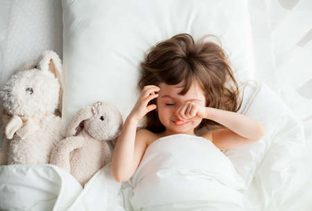 Beautiful little girl rubbing her eyes as she is waking up in a white bed with rabbit toys lying near. Top view.