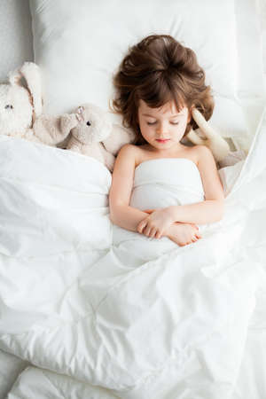 Adorable calm little girl sleeping in white bed with rabbit toys Stockfoto