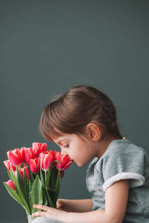 Beautiful little girl sniffing pink tulips in a vase on a gray background