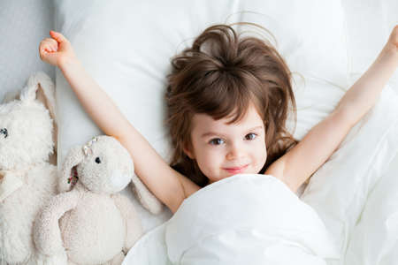 Beautiful little girl stretching hands as she is waking up in a white bed. Top view. Stockfoto