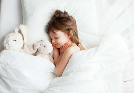 Adorable little girl sleeping sweetly in a white bed with rabbit toys lying near. Top view. Stockfoto