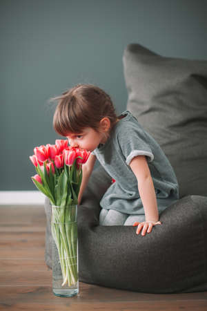 Cute little girl sniffing pink tulips in a vase, sitting on a gray bean bag chair