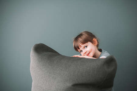 Portrait of a cute little girl with a gray background, hiding behind a gray bean bag chair Stockfoto