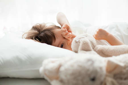 Beautiful little girl rubbing her eyes as she is waking up in a white bed Stockfoto