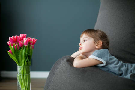 Bored little girl looking at pink tulips in a vase, lying on a gray bean bag chair