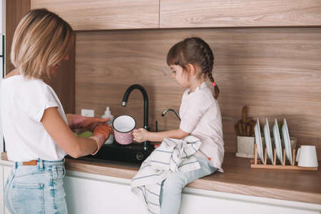 Little girl helping her mother with dishwashing in the kitchen. Woman is washing the dishes, her daughter wiping the cup off with a towel. Stockfoto