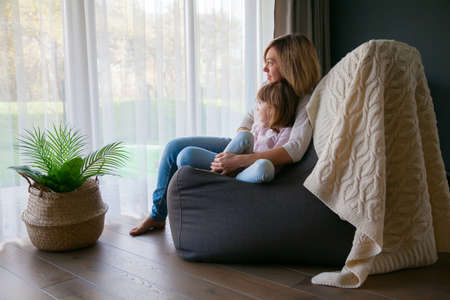 Mother and her little girl sitting cozily on a bean bag chair, hugging and looking through the window