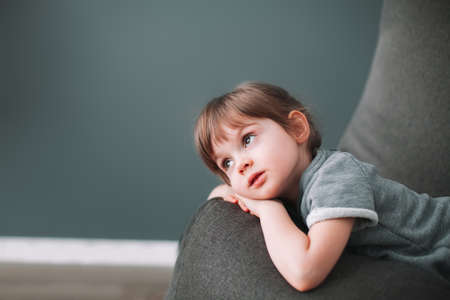 Beautiful little girl with big brown eyes lying on a gray bean bag chair