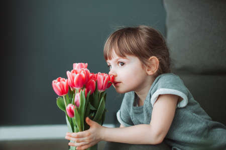 Beautiful little girl sniffing a flower of pink tulip in a vase