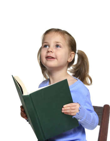 Little girl reading a book looking excitedly up at her teacher or parent Stock Photo - 3596312