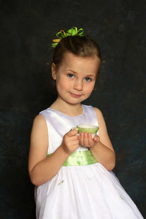 Cute little girl in a white dress holding a tea cup Stock Photo - 3596344