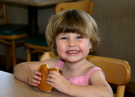 Girl eating hamburger in fast-food restaurant Stock Photo - 3596333
