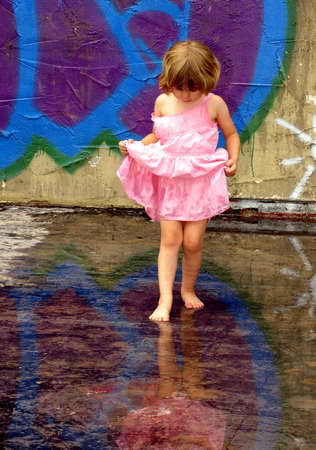 with reflection: Little girl playing in rain puddles with reflections Stock Photo