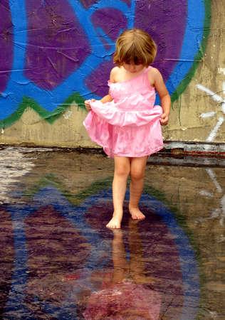 Meisje speelt in regen plassen met weerspiegelingen
