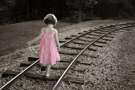 walking alone: Coloreada en blanco y negro con la ni�a en un vestido rosa caminando sobre las v�as del tren  Foto de archivo