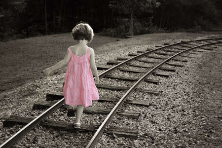 Colorized black and white with little girl in a pink dress walking on railroad track Stock Photo