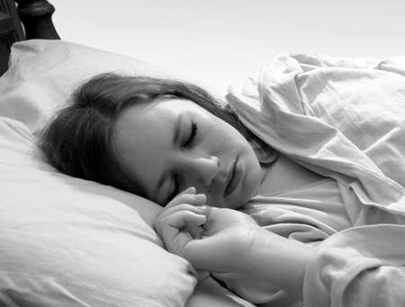 Young woman asleep in bed Stock Photo