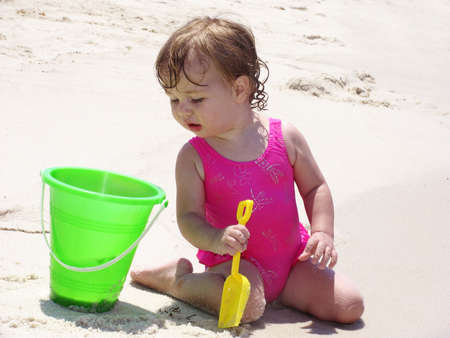 dug: Baby on the beach playing with bucket and shovel in the sand