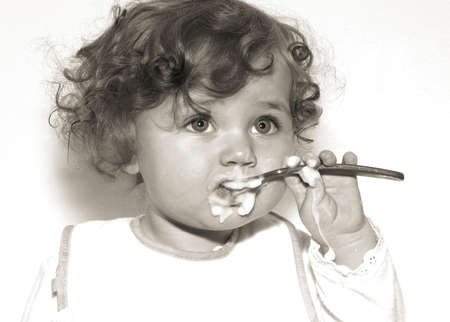 Vintage style black and white of a  messy  eating with a spoon