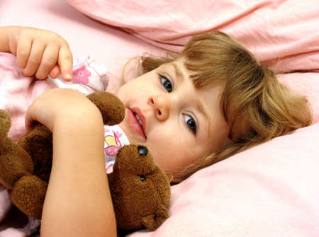 Little girl tucked in bed with her teddybear photo