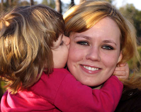 Little girl giving mother a big kiss on the cheek