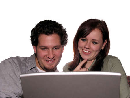 Happy couple looking at laptop computer isolated on white photo