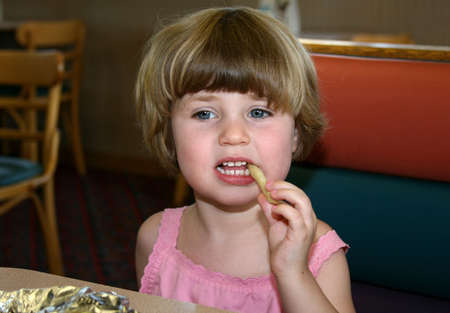 Little girl in fast food restaurant eating fastfood lunch Stock Photo