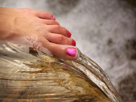 uñas pintadas: La mujer cuidada pie en el borde de una cascada