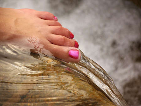 Woman's manicured foot on the edge of a waterfall Stock Photo - 3647268
