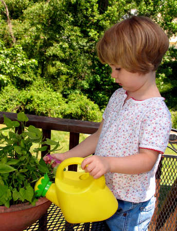 Little girl watering plants