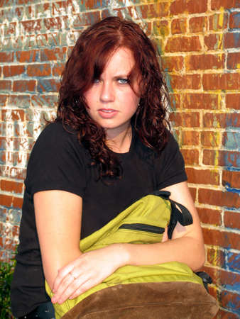 Young confrontational woman holding a bag and looking into camera photo